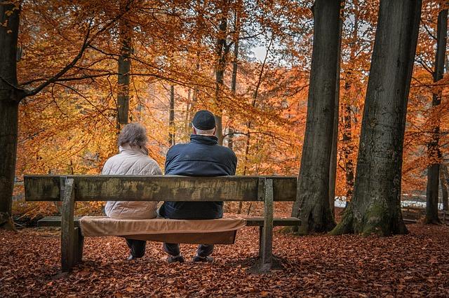 Dvojice sedící na lavičce v podzimním lese